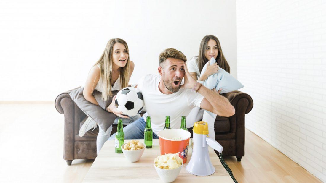 Zwei junge Frauen und ein junger Mann sitzen im Wohnzimmer und fiebern bei einem Fussballspiel mit. Der Mann hat einen Fussball in der Hand.