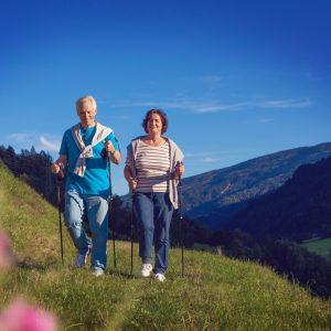 Älteres Paar mit Laufstöcken auf einem Spaziergang in bergiger Natur.