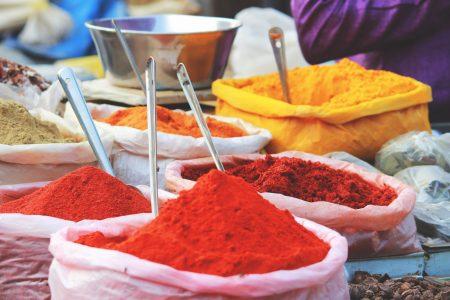 Stoffssäcke gefüllt mit Gewürzpulvern in rot, orange und gelb