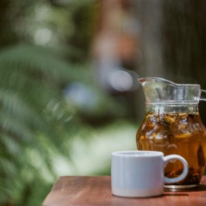 Weisse Tasse auf einem Holzbrett neben einer Kanne mit Tee. Unscharfer Hintergrund aber mit Bäumen.