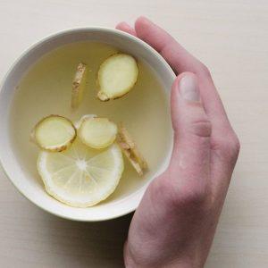 Bild von oben wie eine Hand sich an einer Tasse Tee mit Ingwer und Zitrone wärmt.