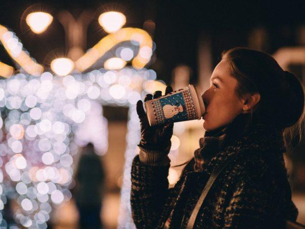 Eine Frau trinkt aus einem Papierbecher und steht in der Nacht vor einem Lichterhintergrund auf der Strasse.
