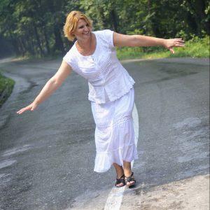 Erwachsene Frau in weissem Kleid balanciert auf einer Strasse auf der Strassenmarkierung.