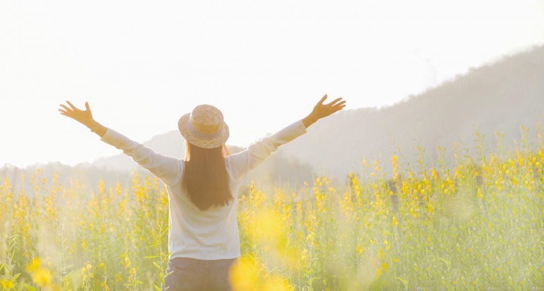 Junge Frau steht zum Horizont mit ausgestreckten Armen in einer grün gelben Blumenwiese.