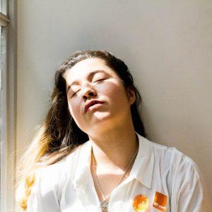 Eine Junge Frau mit langen Haaren, die den Kopf an eine Wand gelehnt hat und die Augen geschlossen hat.