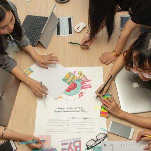 Studenten disskutieren an einem Tisch über ihr Projekt