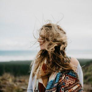 Junge Frau steht in der Natur und ihr Haar wird vom Wind zersaust.
